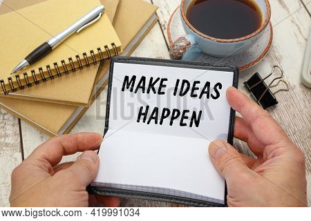 Hands Open A Notebook With The Inscription Make Ideas Happen On The Background Of The Office Desk