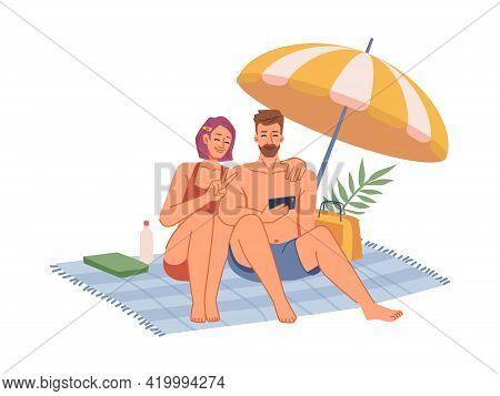 Couple In Swimsuits Sitting On Blanket Under Umbrella, Sunbathing On Beach, Making Selfie On Phone F