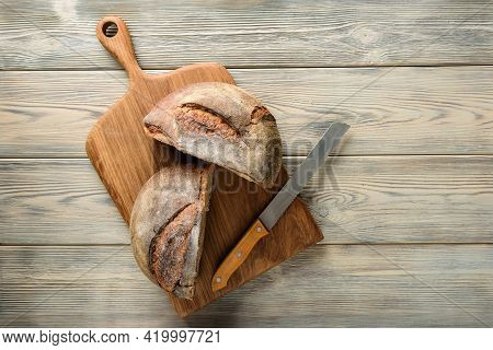 Cutting Board With A Cut Loaf Of Bread. Homemade Bread Cut In Half On A Wooden Table With Copy Space