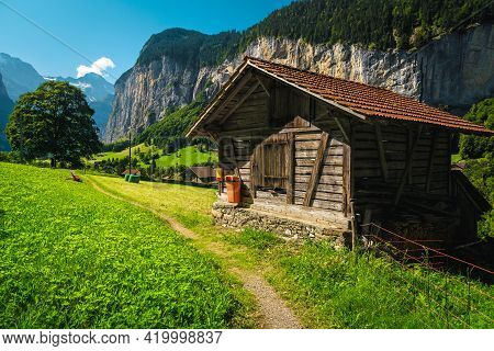 Typical Alpine Wooden Barn On The Green Pasture And High Cliffs In Background, Lauterbrunnen Valley,