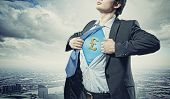 Image of young businessman in superhero suit with pound sign on chest poster