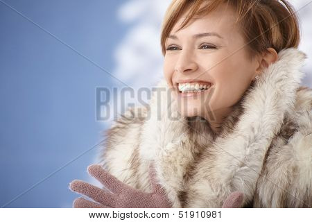 Portrait of happy young woman wearing fur coat, enjoying winter sunshine.