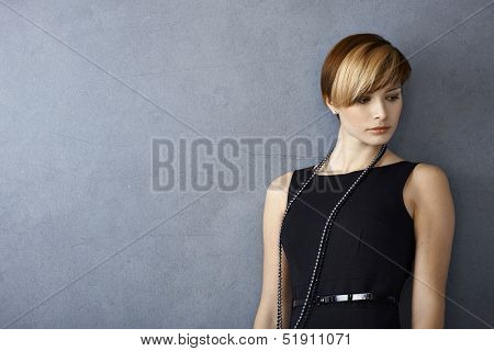 Elegant young woman in black dress leaning to wall, looking serious