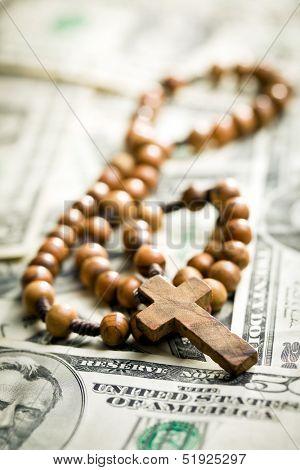 rosary beads lying on us dollars backround