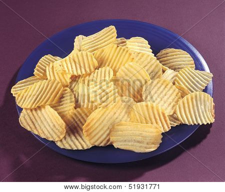 Fresh and salty crinkle chips in plate poster