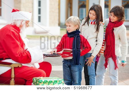 Boy taking biscuits from Santa Claus while children standing in a queue at courtyard