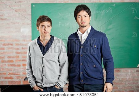 Portrait of confident male students standing against greenboard in classroom
