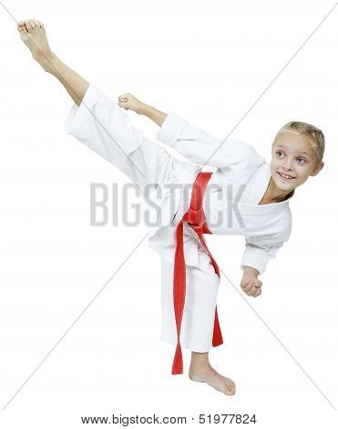 A little girl in a white kimono hits roundhouse kick isolated background