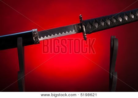 Long japanese sword with a naked blade visible. The background is colored in red. poster
