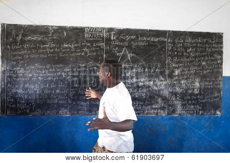 Kinazini, Kenya - July-12: Unidentified African Teacher Is Showing School Work For Tourists On July