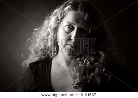Low Key Shot Of A 30S Woman Looking At The Camera