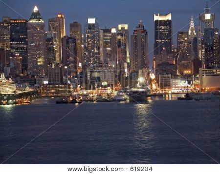 A portion of the New York City skyline at night. poster
