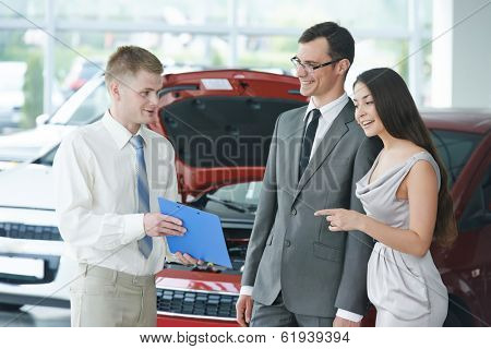 Car salesperson demonstrating rental or new automobile to young woman