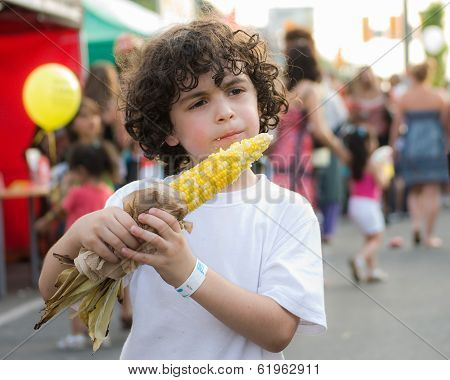 Child Eating Corn In a Festival