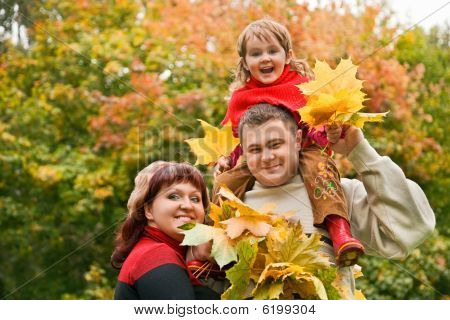 Married Couple And Little Girl Collect Maple Leafs In Park