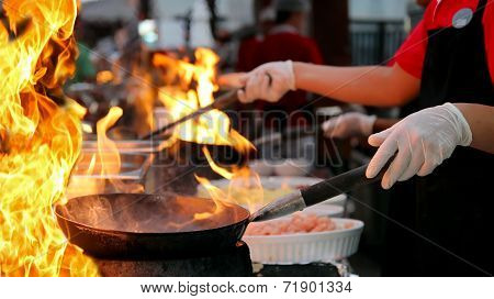 Professional Chef In A Commercial Kitchen Cooking Flambe Style