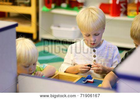 Young Preschool Children Playing Building Blocks In School Classroom