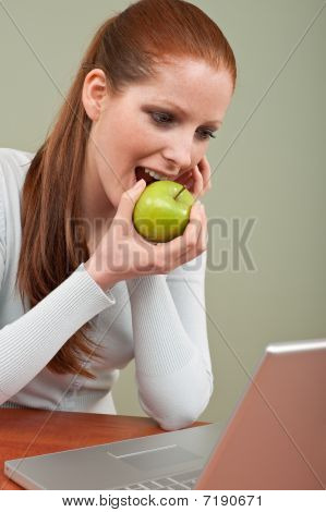 Long Red Hair Woman Biting Apple At Office