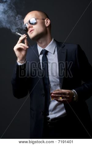 Young Businessman Drinking And Smoking