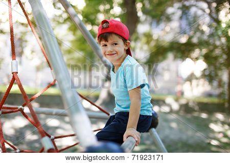 Little Boy In Cap Sit On Jungle Gym