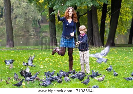 Mother And Son Feeding Pigeons In A Park poster