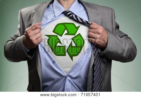 Businessman in classic superman pose tearing his shirt open to reveal t shirt with recycling symbol concept for recycling and environmental conservation