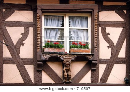 Alsatian window on half-timbering house and small wooden sculpture with geranium. poster
