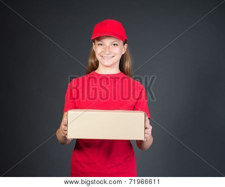 Delivery person delivering package smiling happy in red uniform. Beautiful young woman professional