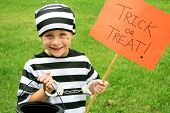 A young American child is dressed up in a prisoner costume on Halloween getting ready to go trick-or-treating. poster