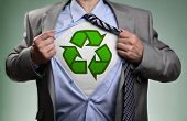 Businessman in classic superman pose tearing his shirt open to reveal t shirt with recycling symbol concept for recycling and environmental conservation poster