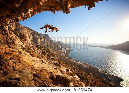 Female rock climber hanging on rope after unsuccessful attempt to take next handhold on cliff while lead climbing poster