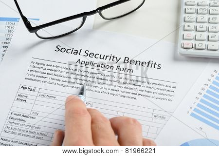 Hand Holding Pen Over Social Security Benefits Form