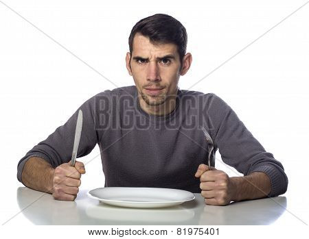 Man at dinner table with fork and knife raised. Hunger strike isolated over white background poster