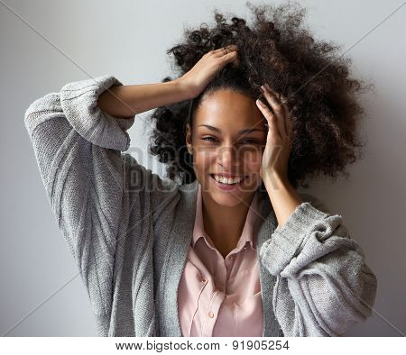 Black Woman Smiling With Hands In Hair
