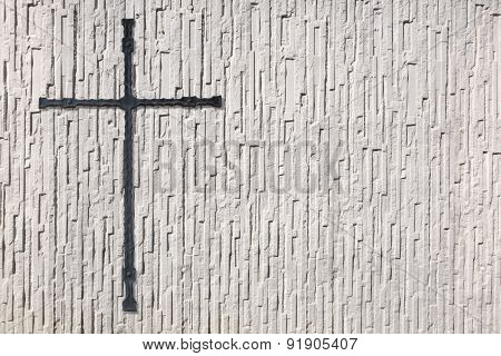 Cross made of metal on a coarse white wall