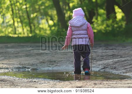 Tree Years Old Girl Walking In Summer Puddle With Thin Tree Twig In Hand