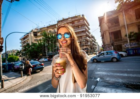 Young woman walking on the street with take away coffee  in the transparent cup in the city poster