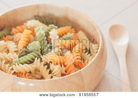Raw Fusilli Pasta On Wooden Bowl