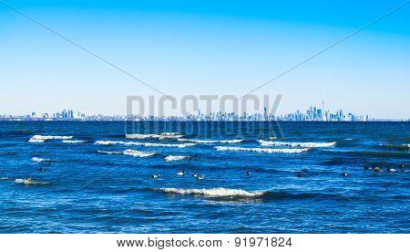 Waves Breaking On Lake With Toronto Skyline On Distant Horizon.