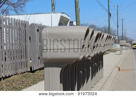 Identical grey mailboxes in a row