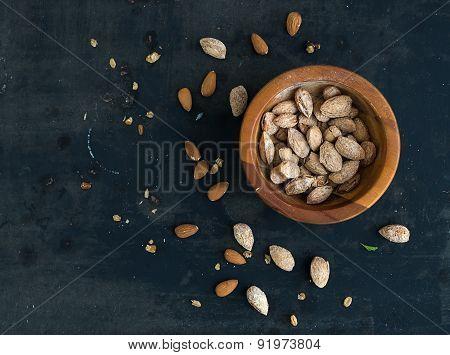 Wooden bowl of salty almond nuts in nutshell grunge dark backdrop, top view