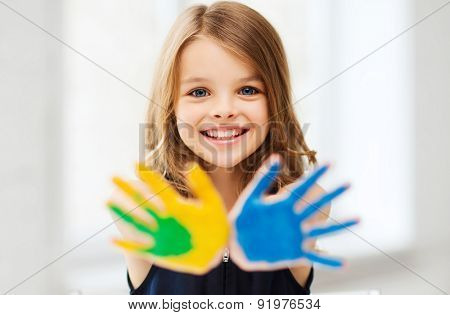 education, school, art and painitng concept - little student girl showing painted hands at school