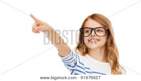 education, school and imaginary screen concept - cute little girl in eyeglasses pointing in the air or imaginary screen