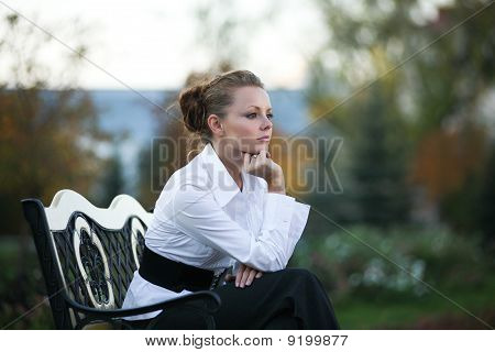Thoughtful Girl On A Park Bench