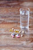 medicine, nutritional supplements and food additives concept - - close up of vitamin pills with cod liver oil capsules and water glass on table poster