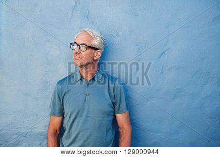 Pensive Mature Man Standing Against A Blue Wall
