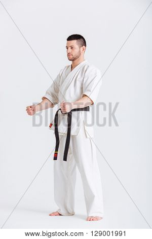 Full length portrait of a man in kimono standing isolated on a white background and loking at camera