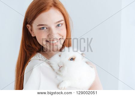 Cheerful redhead woman posing with rabbit isolated on a white background