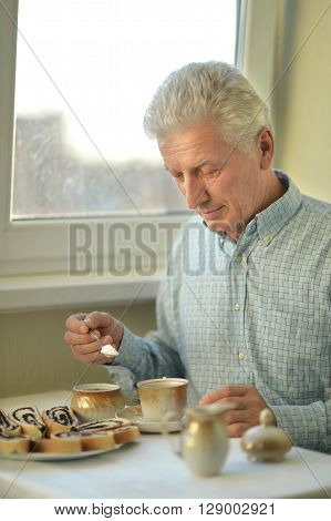 Beautiful elderly man at home with cup of tea