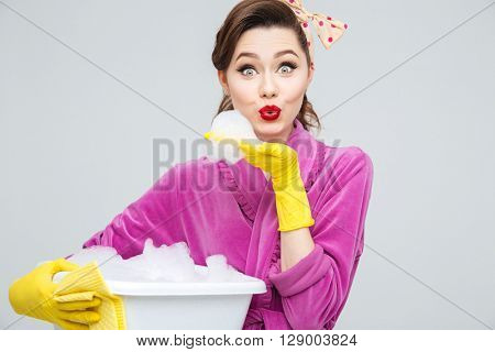Lovely playful young housewife in rubber gloves holding basin with foamed cleanser